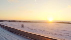 Sunset. Winter landscape. Car on the road. Beautiful snow landscape. winter trees panorama. Sunset. Aerial view. Fly through the field covered with snow stock video