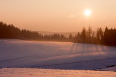 Sunset in winter landscape. Landscape with winter forest and bright sunbeams. Sunrise, sunset in cold snowy landscape Stock Photo