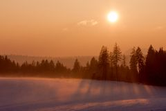 Sunset in winter landscape. Landscape with winter forest and bright sunbeams. Sunrise, sunset in cold snowy landscape Stock Images