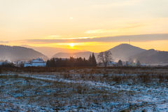 Sunset in winter landscape with houses Royalty Free Stock Image