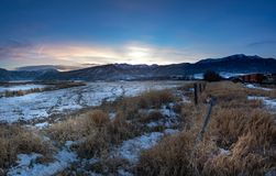 Sunset winter landscape of a rural area with train cars in the snowy tracks royalty free stock images
