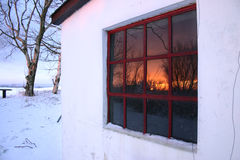 Sunset winter windw. Winter snow covered farm building window reflecting sunset or sunrise in the winter. Taken around christmas in december stock image