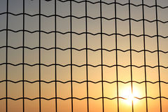 Sunset through a wire mesh Stock Photo