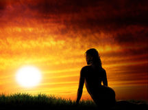 Sunset woman. Nude girl and beautiful sunset Stock Images