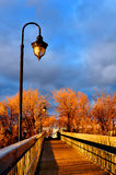 Sunset and wooden bridge. Sun setting over the wooden bridge of a small town on a autumn day Stock Images