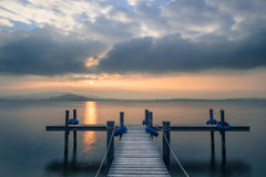 Sunset. Wooden pier on the lake. Fog. Sunset in pastel colors. Long exposure royalty free stock image