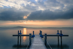 Sunset. Wooden pier on the lake. Fog. Sunset in pastel colors. Long exposure stock photo