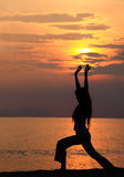 Sunset workout. A woman stretching both arms on the beautiful sunset beach Stock Image