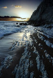 Sunset at Worlbarrow Bay, Dorset. Image of a sunset at Worlbarrow Bay, Dorset. Geological formations, half covered with sand lead the eye through the image royalty free stock photos