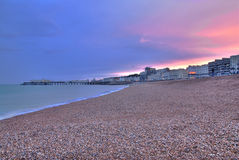 Sunset at Worthing. Beautiful sunset over the sea and pier seen from the beach at Worthing, West Sussex - England Stock Photos