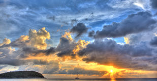 Sunset with Yacht III. Blue and yellow sunset panorama over oceanwith dramatic clouds with island and yacht Stock Photos