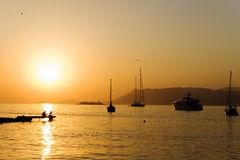 Sunset and yachts. Sunset on the sea with some yachts and two persons on the pier and gull in the sky stock photography
