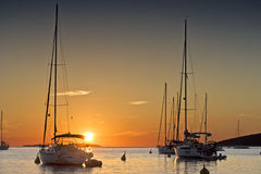 Sunset and yachts. Yachts anchoring near an island Royalty Free Stock Photography