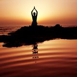 Sunset Yoga. Woman doing yoga at sunset on the seashore