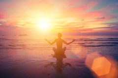 Sunset yoga on the beach, abstract photo about healthy lifestyle. Relax. Stock Photo