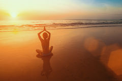 Sunset yoga woman meditation on Ocean coast. Relax. Stock Image