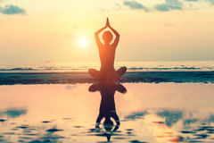 Sunset yoga woman on sea coast. Relax. Stock Photos