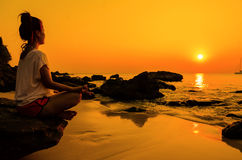 Sunset yoga woman with spirituality on sea coast.  Royalty Free Stock Photography
