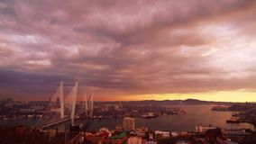 The Sunseton above the Golden Horn bay and the Golden Bridge in Vladivostok from the Eagle Nest mt. stock video footage