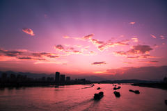 Sunsets. With colorful clouds and sailing boats on the river in China Royalty Free Stock Photography