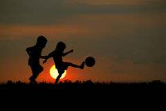Sunsets. The boy play football at sunset stock photography