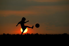 Sunsets. The boy play football at sunset royalty free stock photos