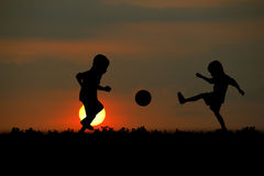 Sunsets. The boy play football at sunset royalty free stock photography