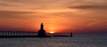 Sunsets On Lake Michigan. This is a Spring picture of a Sunset on Lake Michigan at Michigan City, Indiana. This pictures features the pier light as well as the royalty free stock image