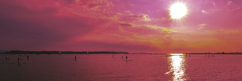 Sunsets over paddlebroaders. Sun sets over paddle broaders in Poole harbour uk stock photography
