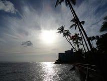 Sunsets over Waikiki waters as waves crash on sea wall at Makale Stock Photography