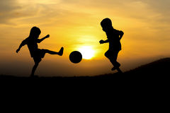 Sunsets. Two boys play football at sunset royalty free stock image