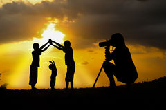 Sunsets. Women and her boys play at sunset royalty free stock photo