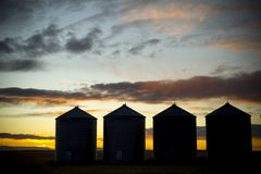 Sunsetting behind four silos. The sun setting and silhouetting four silos in the praries Stock Photos