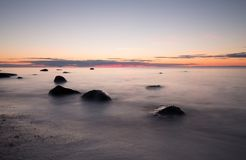 Sunsetting at the coastline. Of the baltic sea. Some rocks can be seen in the water Stock Photography