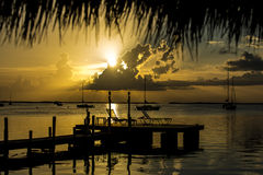 Sunsetting over ocean. Sun setting over ocean in Key Largo into a layer of clouds. A long dock in the foreground with palm tree frawns framing the shot Royalty Free Stock Photo