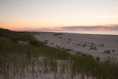 Sunsetting over sand dunes at the beach in a national park in sweden. The sun is setting over the horizon after a summers day Royalty Free Stock Images