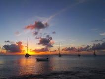 Sunsetting over yachts moored off Kralendijk, Bonaire, Dutch Antilles. Orange sunset over Caribbean sea with yachts in foreground, Kralendijk, Bonaire, Dutch stock photography