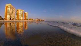 Sunsetting sulla spiaggia con illuminazione dell'oro sugli hotel archivi video