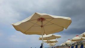 Sunshade ομπρέλα στην παραλία σε μια θυελλώδη νεφελώδη παραλία Κρήτη Tsalos η φιλμ μικρού μήκους