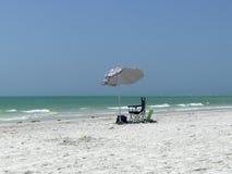 Sunshade on beach. Empty sunshade and chair on the beautiful sunny beach in florida stock photos