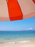 Sunshade on beach with boat Stock Image