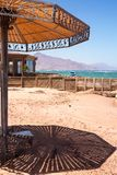 Sunshade on the beach, shade on sand. Coastline of The Red Sea. In Dahab, Sinai, Egypt Royalty Free Stock Photo