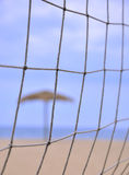 Sunshade behind sand volleyball net on beach Royalty Free Stock Photo