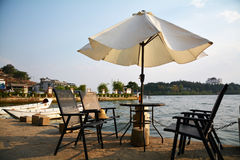 Sunshade and chairs by lake Stock Image
