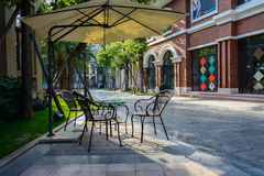 Sunshade and chairs by street in warm afternoon sunlight Stock Images
