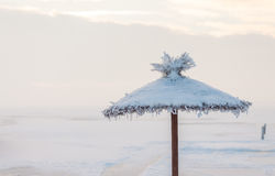 Sunshade covered with snow on the beach in the winter. Sunshade usually associated with summer and heat is covered with snow during winter on the beach Stock Photos