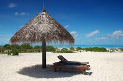 Sunshade with deckchair. On a tropical beach with blue sky and white sand Stock Image