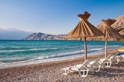 Sunshade i pokładu krzesło na plaży przy Bask w Krk Chorwacja Zdjęcia Stock