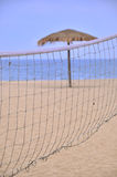Sunshade and sand volleyball net on beach Stock Photography