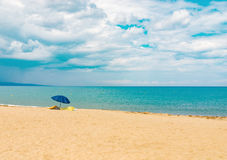 Sunshade on sandy beach sea ocean shore with stormy sky Royalty Free Stock Photo